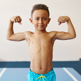 Children, fitness, health and ethnicity concept. Portrait of dark skinned black boy of school age exercising at gym, preparing for competition, posing topless, demonstrating his tensed muscles